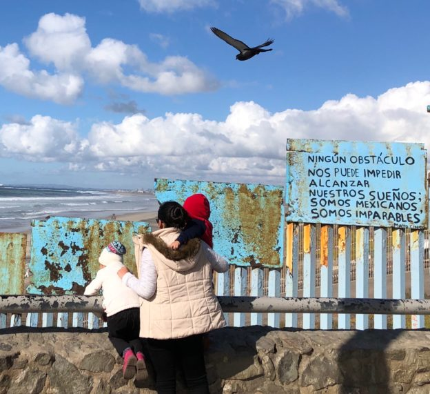 A mother and her two small children stand against the border wall as a gull flies above.